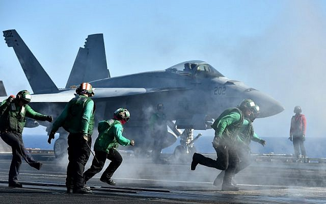 "Sailors get ready around an F/A-18E Super Hornet on the US navy's super carrier USS Dwight D. Eisenhower (CVN-69) (""Ike"") in the Mediterranean Sea on July 6, 2016. (AFP PHOTO / ALBERTO PIZZOLI)"