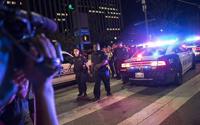 Bystanders stand near police barricades following sniper attacks in Dallas, Texas on July 7, 2016 that killed five cops during a protest late Thursday against police brutality. (AFP Photo/Laura Buckman)