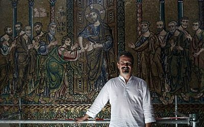 Giammarco Piacenti, CEO of the Piacenti restoration company, poses in front of a renovated mosaic wall inside the Church of the Nativity in the biblical West Bank town of Bethlehem on July 8, 2016. (Thomas Coex/AFP)