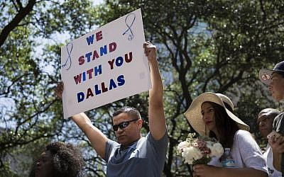 A man holds a sign reading 'We Stand With You Dallas' during a vigil at Thanks-Giving Square in Dallas, Texas, on July 8, 2016, following the shootings during a peaceful protest on July 7 that left 5 police officers dead. (AFP PHOTO/Laura Buckman)