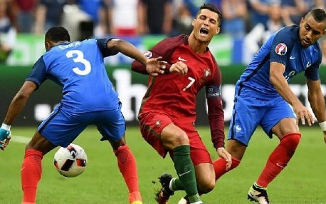 da84bcc5137 France s forward Dimitri Payet (R) looks on as Portugal s forward Cristiano  Ronaldo falls onto
