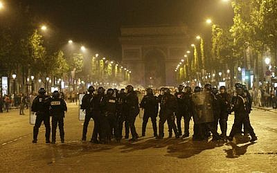 French riot police stand near the Arc de Triomphe after the Euro 2016 final football match between Portugal and France on the Champs Elysees in Paris, on July 10, 2016. (AFP PHOTO/GEOFFROY VAN DER HASSELT)