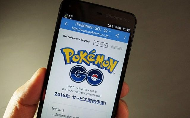 """This photo illustration taken in Tokyo on July 13, 2016 shows the Pokemon official site through a Japanese internet website announcing the latest information for """"Pokémon GO"""".(AFP PHOTO / KAZUHIRO NOGI )"""