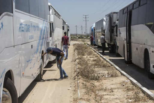 Buses received on the Palestinian side of the Israeli border terminal of Erez in the Gaza strip in the first such delivery since Israeli imposed a blockade on Gaza in 2007, seen here on July 13, 2016. (AFP/MAHMUD HAMS)
