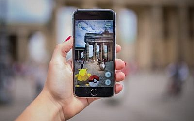 A woman points her smartphone at the Brandenburg Gate as she plays the Pokemon Go mobile game in Berlin on July 13, 2016. (AFP/ dpa / Sophia Kembowski)
