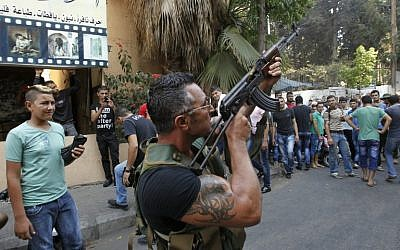 A Lebanese gunman during the funeral procession of Hamad al-Moqdad, one of the Lebanese victims of a car bomb attack that killed dozens in a Beirut stronghold of terror group Hezbollah on August 16, 2013.(AFP PHOTO / ANWAR AMRO )