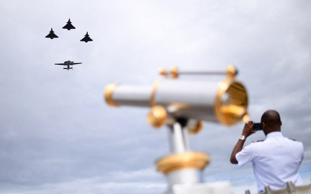 A man takes a picture as three Rafale M fighter jets fly ahead of an E2C during the annual Bastille Day military parade on the Champs-Elysees avenue in Paris on July 14, 2016. (AFP/ STEPHANE DE SAKUTIN)