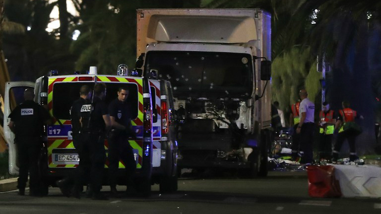 Police officers and rescue workers stand near a van that plowed into a crowd leaving a fireworks display in the French Riviera town of Nice on July 14, 2016. (Valery Hache/AFP)