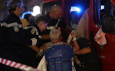 Rescue workers help an injured woman into an ambulance after a truck drove into a crowd watching a fireworks display in Nice, France, on July 15, 2016. (AFP/Valery Hache)