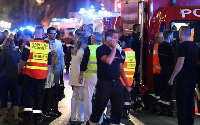 Police officers, firefighters and rescue workers are seen at the site of an attack on the Promenade des Anglais on July 15, 2016, after a truck drove into a crowd watching a fireworks display in the French Riviera town of Nice. (AFP PHOTO / Valery HACHE)