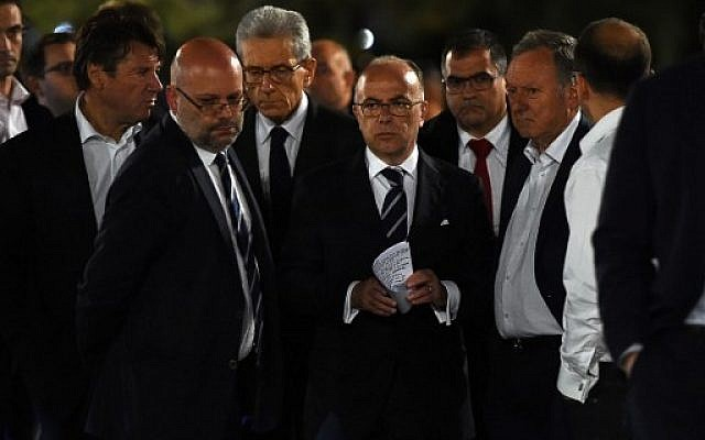 French Interior Minister Bernard Cazeneuve, center, arrives to speak to the media in Nice early on July 15, 2016 as he visits the area where a truck ploughed into a crowd of people during Bastille Day celebrations. (AFP Photo/Anne-Christine Poujoulat)