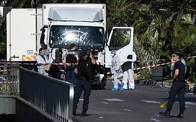 Forensics officers and policemen look for evidence in a truck on the Promenade des Anglais in the French Riviera town of Nice on July 15, 2016, after the truck plowed through a crowd watching a fireworks display. (AFP/Anne-Christine Poujoulat)