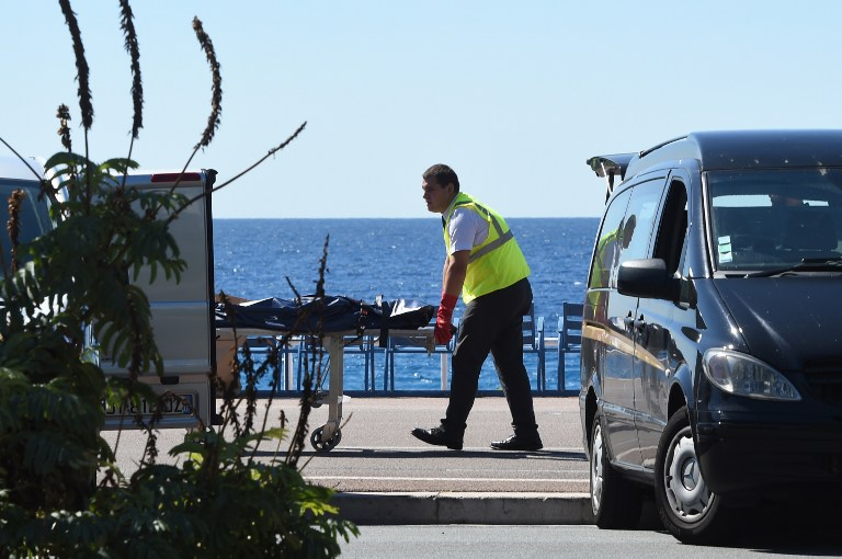 A forensic expert evacuates a dead body on the Promenade des Anglais seafront in the French Riviera city of Nice on July 15, 2016, after a gunman smashed a truck into a crowd of revellers celebrating Bastille Day, killing at least 84 people. (AFP Photo/Boris Horvat)