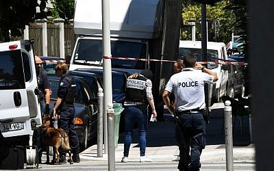 French police officers and French gendarmes stand next to a truck in a street of Nice on July 15, 2016, near the building where the man who drove a truck into a crowd watching a fireworks display, the day before, reportedly lived. (AFP Photo/Anne-Christine Poujoulat)