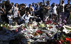 People lay flowers in the street of Nice to pay tribute to the victims the day after a gunman smashed a truck into a crowd of revellers celebrating Bastille Day, killing at least 84 people, on July 15, 2016. (AFP Photo/Anne-Christine Poujoulat)