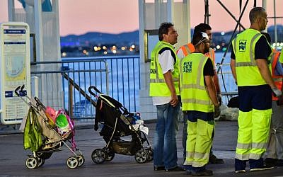 Garbage collectors gather near abandoned baby strollers, as they prepare to clean the Promenade des Anglais on July 15, 2016 in Nice, on the day following the deadly Bastille Day celebration attack. (AFP PHOTO/GIUSEPPE CACACE)