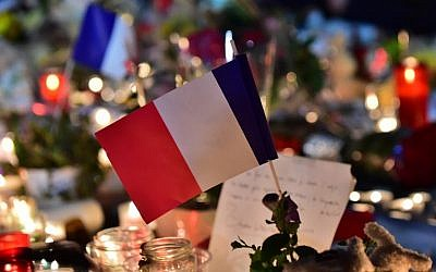 This photo taken on July 15, 2016 in Nice, shows a French flag at a make-shift memorial for victims of the deadly Bastille Day attack in the city that killed 84 people and some 200 more.  (AFP PHOTO/GIUSEPPE CACACE)