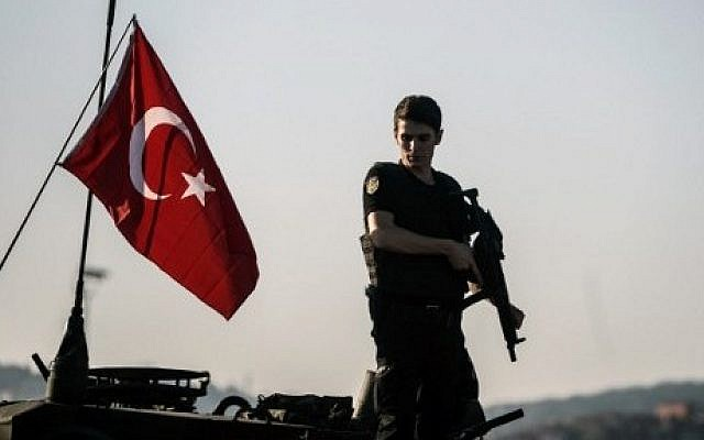 A Turkish anti-riot police officer stands guard on a tank after a military position on the Bosphorus bridge was taken over in Istanbul on July 16, 2016. (AFP Photo/Ozan Kose)