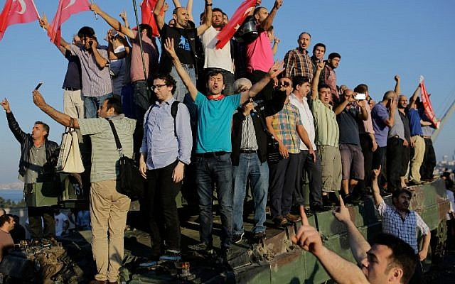 People celebrate on a tank after they took over military position on the Bosphorus bridge in Istanbul on July 16, 2016, folowing a failed army coup. (AFP PHOTO/Yasin AKGUL)