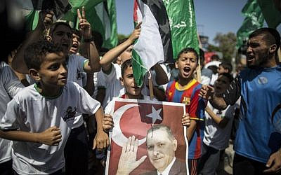 Palestinian supporters of the Hamas movement hold portraits of Turkish President Recep Tayyip Erdogan as they shout slogans against the military coup attempt in Turkey, during a demonstration in Gaza City, on July 16, 2016. (AFP PHOTO/MAHMUD HAMS)