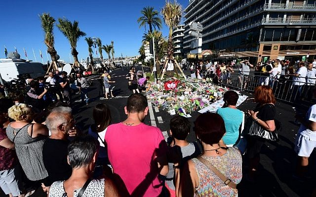 People lay flowers, candles and messages at a makeshift memorial in Nice on July 16, 2016, in tribute to the victims of the Bastille Day attack on the Promenade des Anglais seafront which killed 84 people. (AFP PHOTO/GIUSEPPE CACACE)