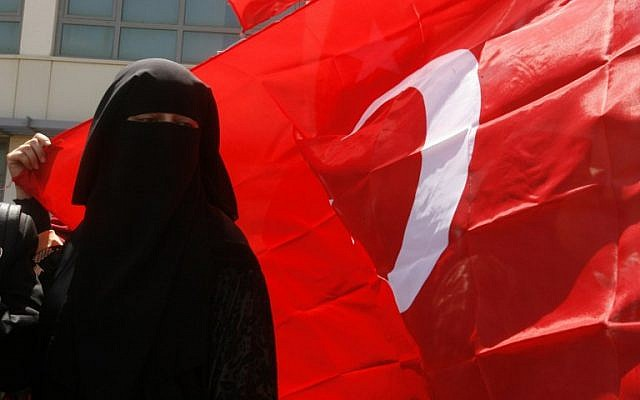 A Lebanese woman holds a Turkish flag during a demonstration by members of the Islamic group Jamaa Islamiya in the southern Lebanese port city of Sidon on July 16, 2016, to support Turkish President Recep Tayyip Erdogan following a deadly but foiled coup attempt. (AFP PHOTO/MAHMOUD ZAYYAT)