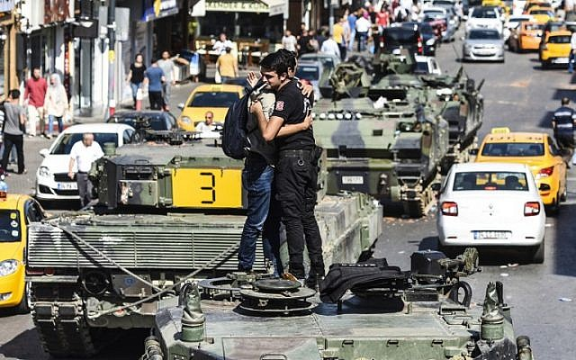 A Turkish police officer embraces a man on a tank after the military position was taken over in Istanbul on July 16, 2016, following a failed army coup. (AFP PHOTO/BULENT KILIC)