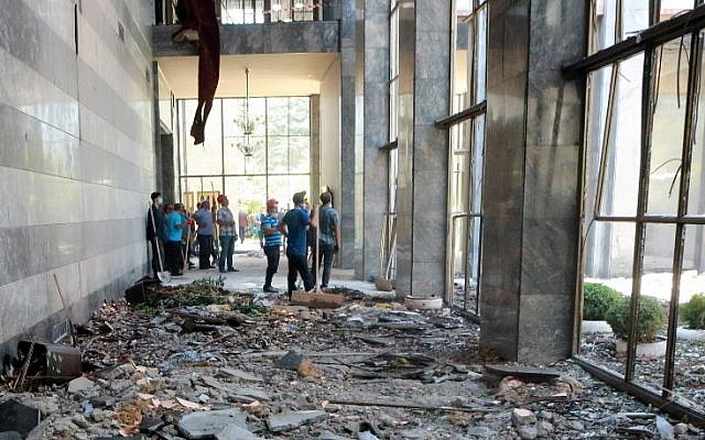 Workers inspect and clear debris in the Grand National Assembly of Turkey on July 16, 2016 in Ankara, after it was bombed by rebel jets during a failed military coup. (AFP PHOTO/ADEM ALTAN)