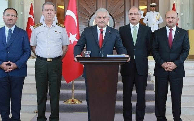 Turkish Prime Minister Binali Yildirim (C), flanked by Turkish Justice Minister Bekir Bozdag (L), Chief of the General Staff of the Turkish Armed Forces Hulusi Akar (2nd L), Turkish Interior Minister Efkan Ala (2nd R) and Turkish Defence Minister Fikri Isik (R), gives a press conference outside the Cankaya Palace in Ankara, on July 16, 2016.  (AFP PHOTO/ADEM ALTAN)