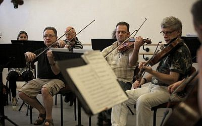 "The Israel Camerata Jerusalem Orchestra play instruments from the ""Violins of Hope"" project from the collection of Amnon and Avshalom Weinstein who restore instruments that survived the Holocaust on July 13, 2016. (AFP PHOTO / MENAHEM KAHANA)"