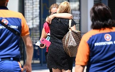 Women comfort each other outside Pasteur Hospital in the French Riviera town of Nice on July 16, 2016, after the July 14 truck attack that killed 84 people on France's national holiday. (AFP Photo/Anne-Christine Poujoulat)