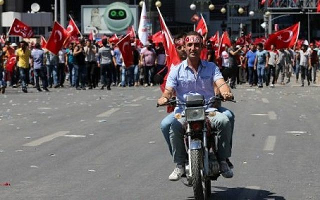 Two men ride a motorcycle as people march from Kizilay square towards the Turkish General Staff building in Ankara, on July 16, 2016, following a failed coup attempt. (AFP PHOTO / ADEM ALTAN)