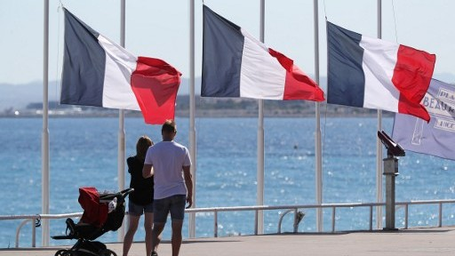 People pass French flags lowered at half-mast in Nice on July 16, 2016, following the deadly Bastille Day attack. (AFP PHOTO / Valery HACHE)