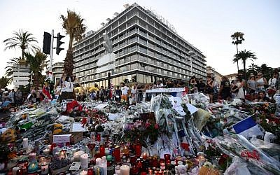 This photo taken on July 16, 2016 in front of Le Meridien hotel in Nice, southern France, shows people gathering around flowers and candles placed in the road for victims of the deadly Bastille Day attack.(AFP PHOTO / ANNE-CHRISTINE POUJOULAT)