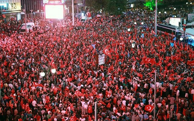 People wave flags as they gather in Kizilay Square in Ankara on July 16, 2016 during a demonstration in support of the Turkish president. President Recep Tayyip Erdogan regained control over Turkey after a coup attempt. (AFP PHOTO / ADEM ALTAN)