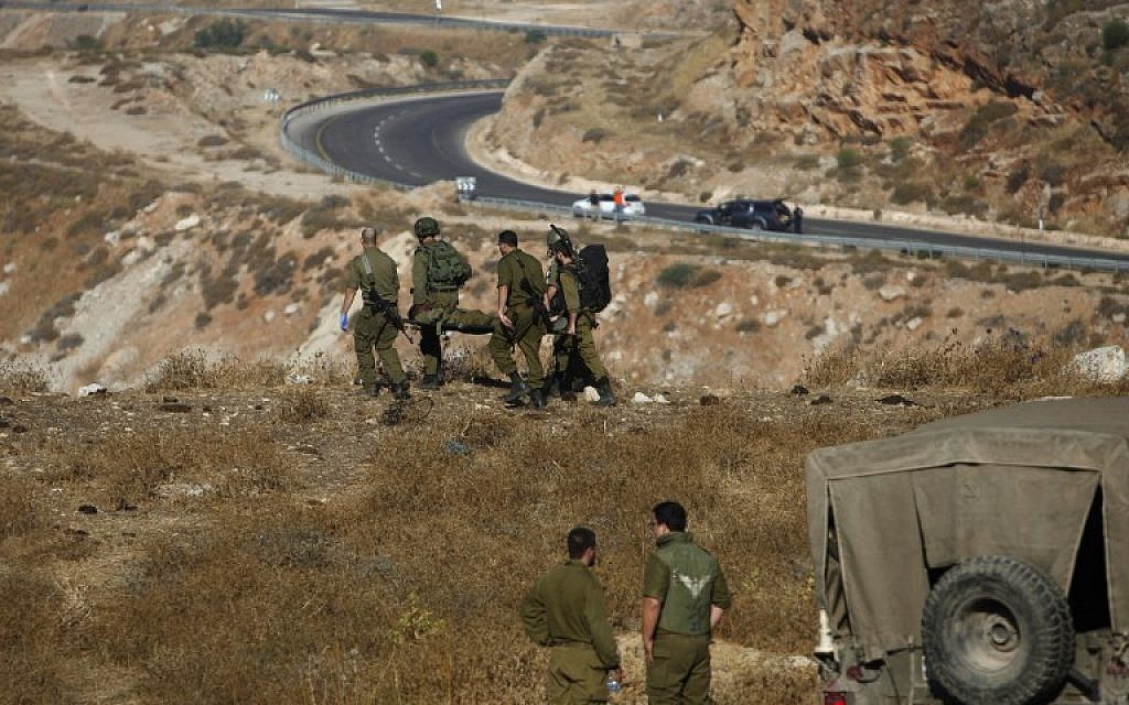 Israeli soldiers evacuate a wounded soldier following a grenade explosion near the village of Majdal Shams in the Golan Heights on July 17, 2016. (AFP / JALAA MAREY)