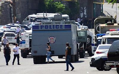 Armenian police officers block the streets to Erebuni police station in Yerevan. An armed group with links to an imprisoned opposition leader seized a police building in Yerevan and took hostages, according to Armenia's National Security Service. One of the gunmen said the hostages included the country's deputy police chief. (AFP PHOTO / KAREN MINASYAN)