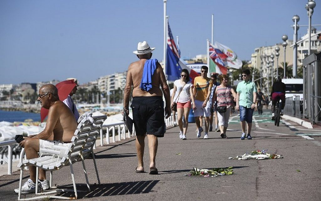 People walk on the Promenade des Anglais next to flowers left as a tribute to victims of the Bastille day deadly attack on July 17, 2016 in Nice. (AFP/ANNE-CHRISTINE POUJOULAT)