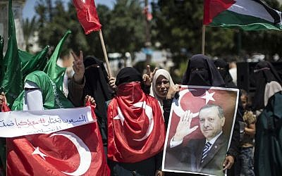 Palestinian supporters of the Hamas movement hold portraits of Turkish President Recep Tayyip Erdogan as they shout slogans against the military coup attempt in Turkey, during a demonstration in Gaza City, on July 17, 2016. (AFP/MAHMUD HAMS)