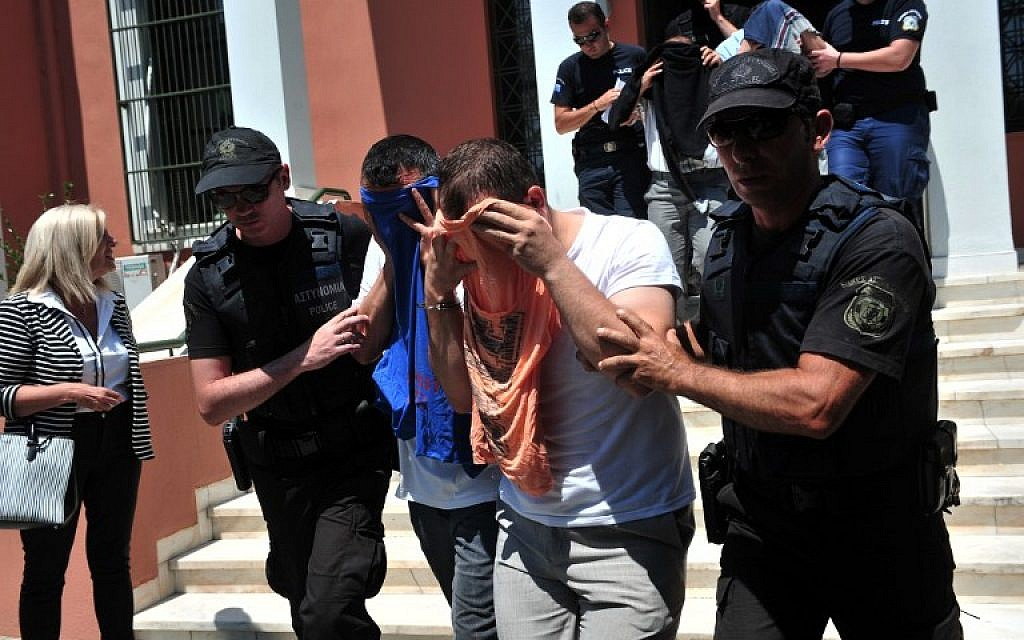 Turkish officers escorted by Greek police officers leave the courthouse of Alexandroupoli after appearing before a Greek prosecutor, on July 17, 2016.  The eight, who have claimed asylum in Greece, arrived by military helicopter on July 16, 2016 after sending a distress signal to authorities at the airport in northern Alexandroupoli.  (AFP/SAKIS MITROLIDIS)