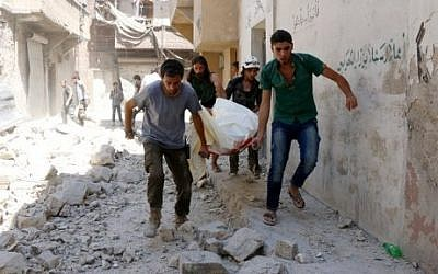 Illustrative image of Syrians evacuating a body on a stretcher following airstrikes on the rebel-controlled neighborhood of Maysar in the northern Syrian city of Aleppo, on July 17, 2016. (AFP/Thaer Mohammed)