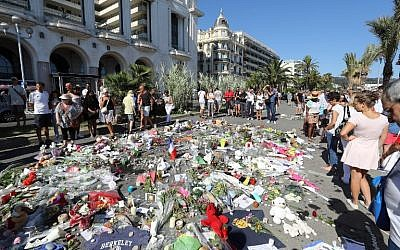 People gather near flowers placed at a makeshift memorial near the Promenade des Anglais in Nice on July 17, 2016, in tribute to the victims of the Bastille Day attack that left 84 dead.(AFP PHOTO / Valery HACHE)