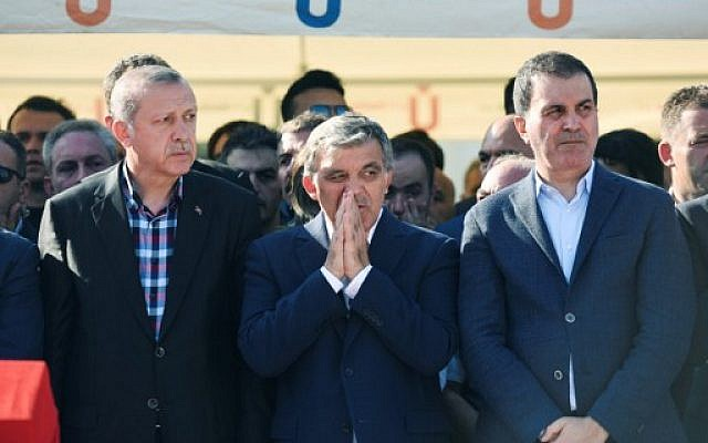 Turkey's President Recep Tayyip Erdogan (L) and former Turkish president Abdullah Gul (C) react after attending the funeral of a victim of the coup attempt in Istanbul on July 17, 2016. (AFP PHOTO/BULENT KILIC)