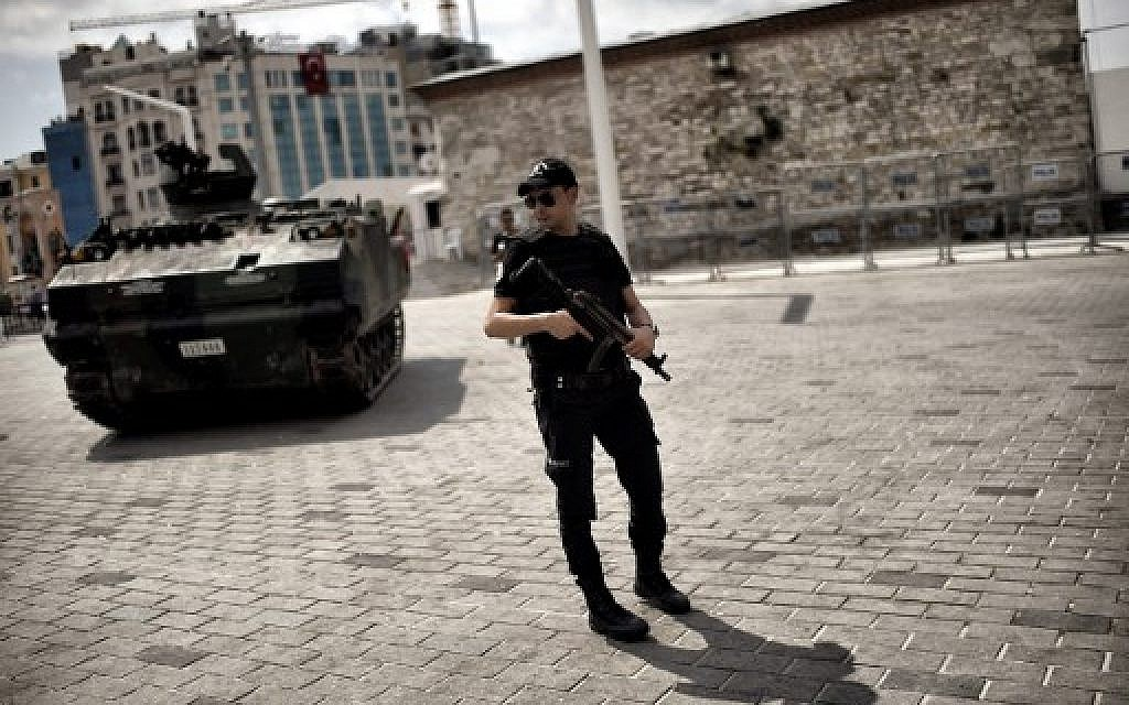 A police officer stands next to an armoured vehicle that was used by soldiers during the coup attempt at Taksim square in Istanbul on July 17, 2016. (AFP PHOTO / ARIS MESSINIS)