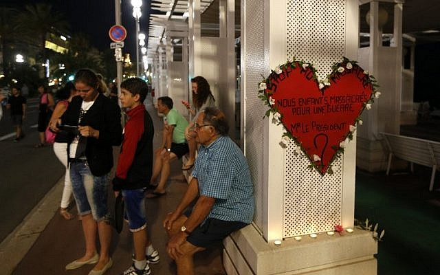 "A man sits next to a heart-shaped sign reading ""Stop the massacre...Our children massacred for a war...Mr. President?"" on the Promenade des Anglais in Nice on July 17, 2016.(AFP PHOTO / Valery HACHE)"