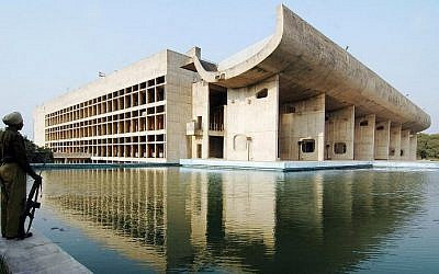 An Indian guard stands beside the Assembly Building, designed by Le Corbusier, in the Indian city of Chandigarh. UNESCO on July 17, 2016 listed Franco-Swiss architect Le Corbusier's works -- including the Indian city of Chandigarh which he planned in the 1950s -- among its World Heritage Sites. (AFP PHOTO / NARINDER NANU)