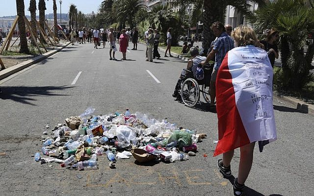 """People throw garbage on the Promenade des Anglais seafront in Nice, at the site where the 31-year-old Tunisian, Mohamed Lahouaiej-Bouhlel, drove a truck into a crowd watching a fireworks display on Bastille Day, was killed by the police, on July 18, 2016. The message reads """"coward."""" (AFP/ Valery HACHE)"""