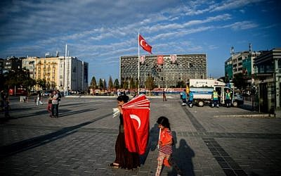 A woman prepares to sell Turkish flags in Taksim square on July 18, 2016 in Istanbul. (AFP PHOTO / OZAN KOSE)