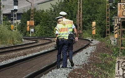 Police officers walk along train tracks in Wuerzburg southern Germany on July 19, 2016, a day after a man attacked train passengers with an ax. (AFP PHOTO / DANIEL ROLAND)
