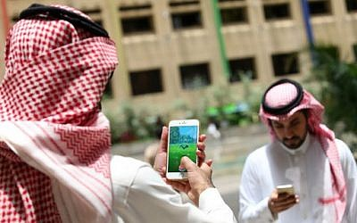 Saudi men play with the Pokemon Go app on their mobile phones in Riyadh, the Saudi Arabian capital on July 17, 2016.  (AFP PHOTO / STRINGER)